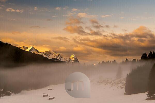 Zugspitze, Alpspitze und Wettersteingebirge am frühen Morgen. Im Vordergrund einige kleine Heuschober, Holzhütten und Nebel, während das Morgenrot die Schnee Landschaft in warme orangetöne taucht.