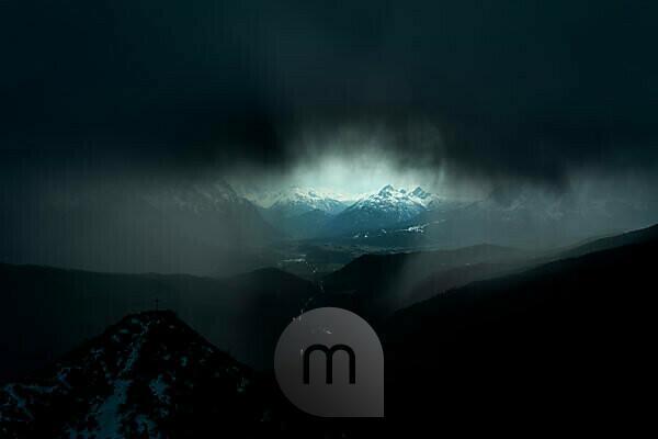 Unwetter über dem Isartal. Unwetter mit dem Gipfelkreuz/ Bergspitze des Martinkopf, etwas unterhalb des Herzogstandes im Estergebirge, den bayrischen Voralpen. Eine dunkle schwere Gewitterwolke und Regen, lassen nur ein kleines Sichtfenster nach Mittenwald, Wallgau und das Wettersteingebirge zu.