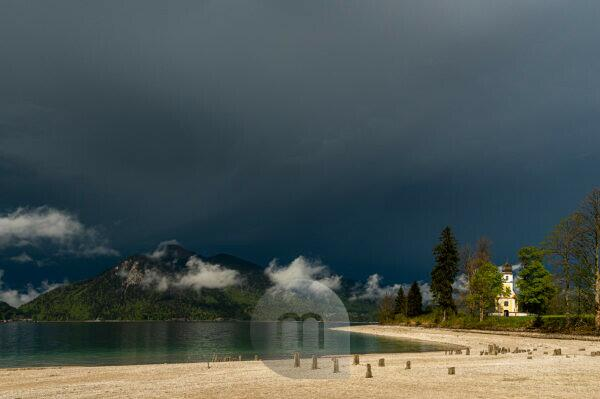 Old wooden planks on the Zwergern peninsula in the Walchensee in the Bavarian Prealps during severe weather. The wooden planks probably come from a historic fish or crab breeding. In the background the small chapel of St. Margareth and dramatic clouds over the Walchensee and Jochberg.