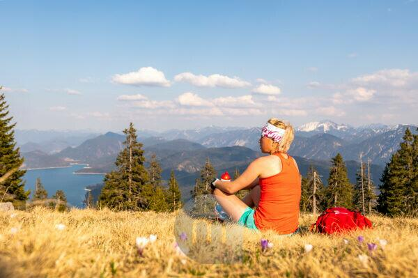 Trail runner Katharina Kirschner enjoys the view of the Walchensee and the mountains of the German Alps during a sport break