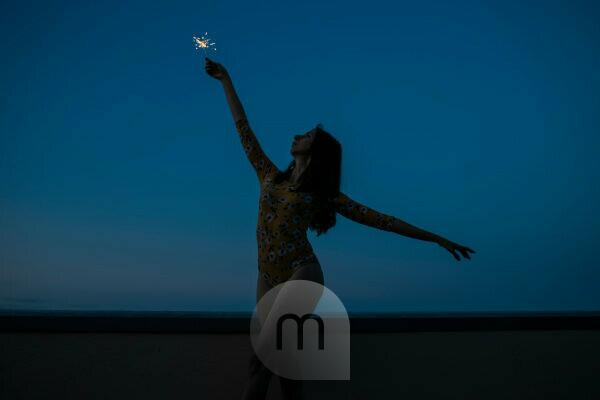 Carefree woman holding sparkler while standing at building terrace against clear blue sky during sunset