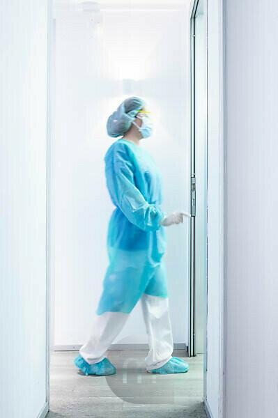 Mature female dentist walking in illuminated hallway