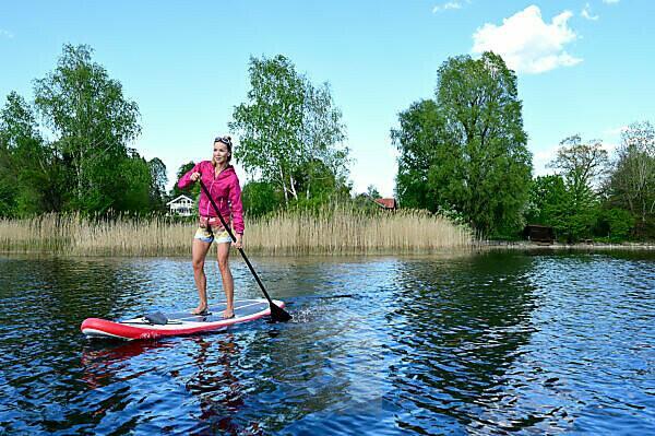 Woman stand up paddling on Lake Staffelsee, Bavaria, Germany