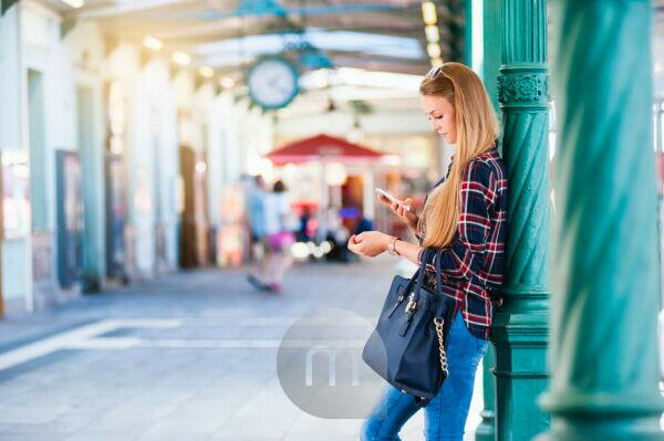 Young woman leaning against column looking at smartphone