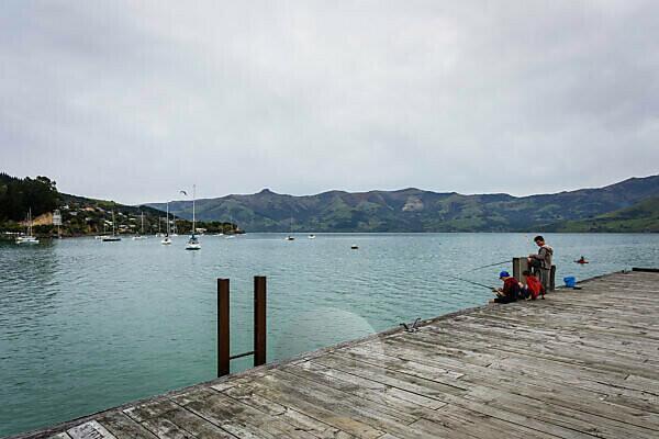 Boys fishing in the harbor in Akaroa