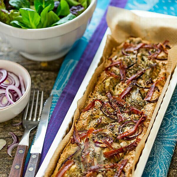 Foccacia frisch aus dem Ofen, in einer rechteckigen Tarteform, mit grünem Salat, extra roten Zwiebeln und Artischocken