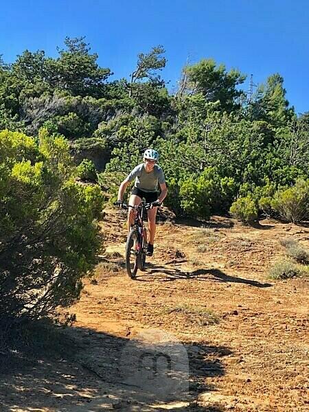 Young person, cycling, mountain bike, nature, sport, Mediterranean, summer, sun, blue sky,