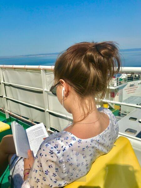 Ferry, morning light, book, reading, headphones, Mediterranean Sea, glasses, music, sitting, young woman, dress, sun, railing, sky