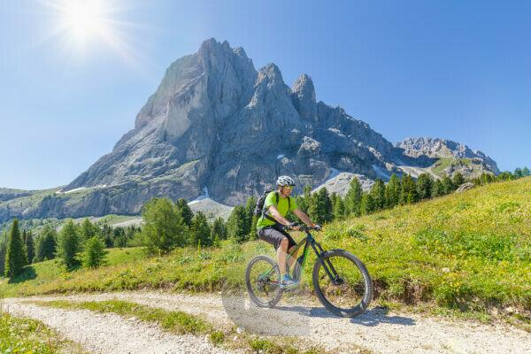 cyclist with an electric mountain bike (e-bike) pedaling at the foot of Sassolungo Langkofel, Val Gardena, Grödental, South Tyrol, Dolomites, Italy