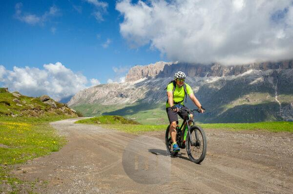 cyclist with an electric mountain bike (e-bike) along the trail Viel del Pan (Bindelweg) in front of the Sella group, on the borders between Veneto and Trentino Alto Adige, Dolomites, Italy