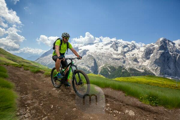 cyclist with an electric mountain bike (e-bike) along the trail Viel del Pan (Bindelweg) in front of the Marmolada, Padon ridge on the borders between Veneto and Trentino Alto Adige, Dolomites, Italy