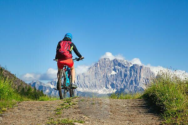 woman pedaling towards the Civetta mountain near Cherz alm, tour with e-bike in the natural landscape of Dolomites, livinallongo del col di lana, belluno, veneto, italy