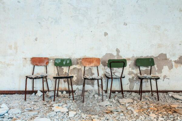five small chairs side by side in an old abandoned building, rubble and dust, peeling wall