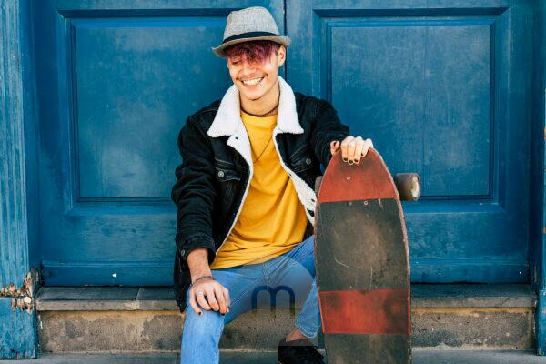 Cheerful and happy teenager sit down outside home with blue old door in background - city urban lifestyle and trendy generation z people concept - youthful and joy model with skateboard