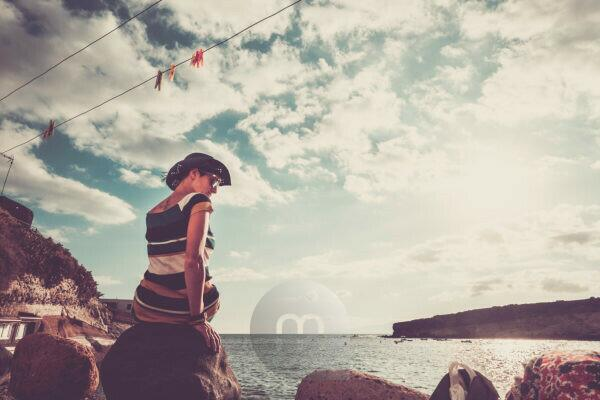 Loneliness and depression concept image with one young woman sit down alone at the beach