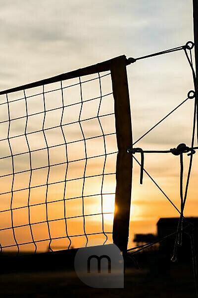 Beach volleyball - a backlit net at sunset