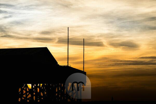 Colorful sunset on the North Sea - in the backlight of the sun a typical stilt house, pile dwellings, pile dwellings that defy the tides.