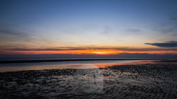 Relaxation on the Wadden Sea and on the beach of St. Peter Ording, North Sea at sunset.
