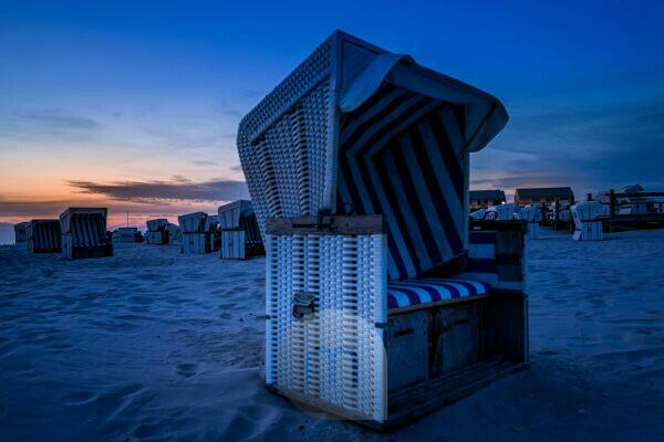 Relaxation in a beach chair. The North Sea at sunset. Wadden Sea and Beach