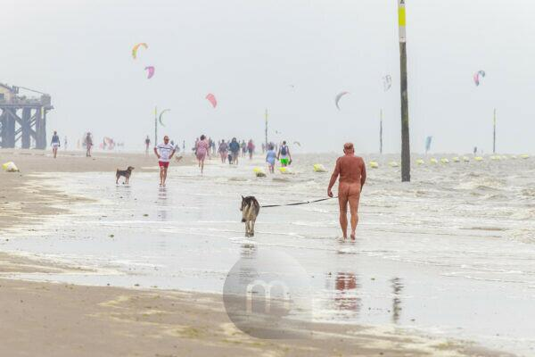 A man walks naked on the beach with his dog