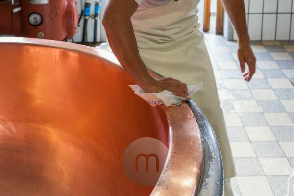 dairymaid porcesses fresh milk to aromatic alp cheese, The milk pot is cleaned carefully - Kesseltanz,