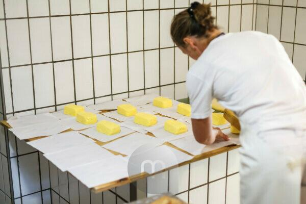 Production of butter, processing, dairymaid while packing the pieces of one pound