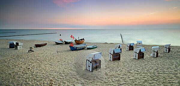 Deutschland, Mecklenburg-Vorpommern, Insel Usedom, Ostseebad Kölpinsee, Strandkörbe und Fischerboote am Strand bei Sonnenaufgang,