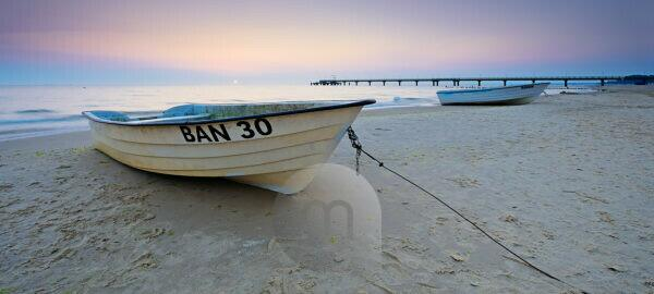 Germany, Mecklenburg-Western Pomerania, Usedom island, Ostseebad Bansin, fishing boats on the beach at sunrise, behind it the sea bridge
