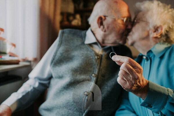 older couple, kiss, woman holds wedding ring into camera,