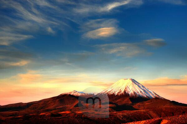 The cone of the Mt. Ngauruhoe in the Tongariro national park. The volcano is overcast with snow during a magnificent sundown.