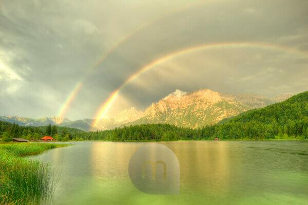 Double rainbow about the northern Karwendelgebirge (mountains) over Mittenwald. The water surface of the Lautersee (lake) is easily curled by beginning rain. On the left in the picture there is the red roof of a small outdoor swimming pool with kiosk, on the right the water guard small house.