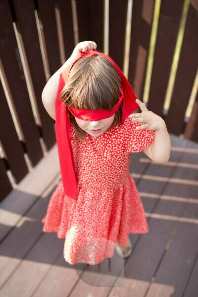 4-6 years old girl in red dress and red blindfold