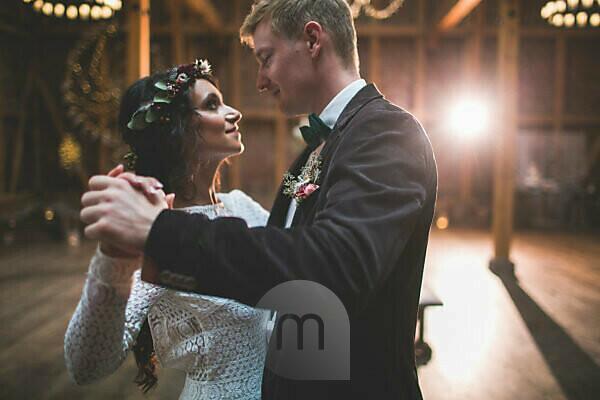 Brautpaar tanzt bei Hochzeitsfeier in einer Scheune