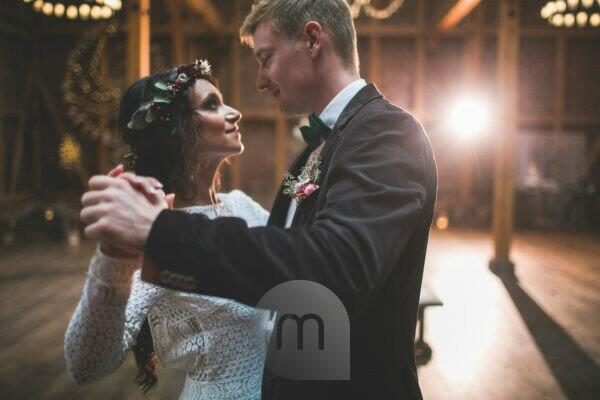 Bride and groom dances at wedding celebration in a barn