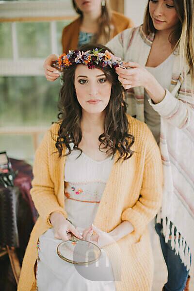 Alternative wedding, preparation, girlfriends decorate bride with floral wreath