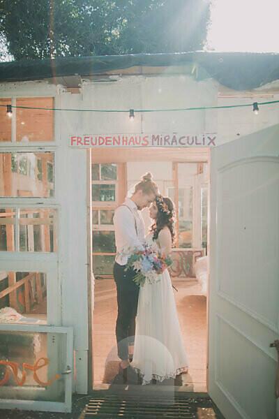 Bride and groom at alternative wedding in garden pavilion