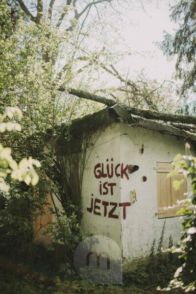 Old decayed garden house with the inscription 'Glück ist Jetzt' (Happiness is now)