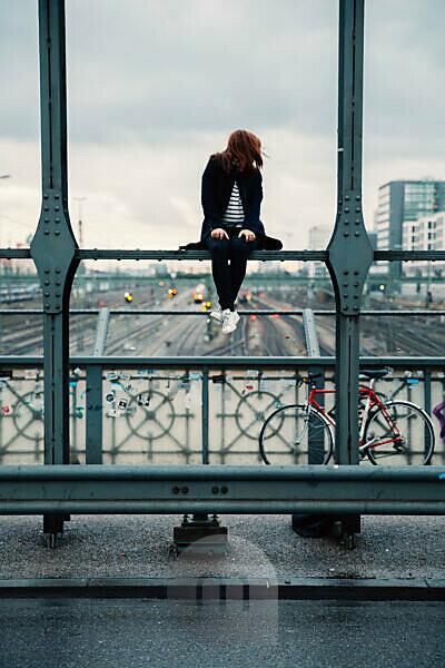 Frau sitzt auf Eisenbahnbrücke, München, Bayern, Deutschland