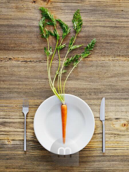 Carrot on plate, cutlery, knife and fork on old wooden table, from above