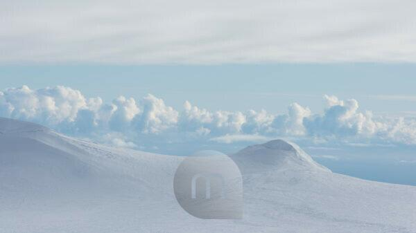 Icelandic snow-covered landscape, bird's eye view, volcanic mountains and the Atlantic Ocean in the background