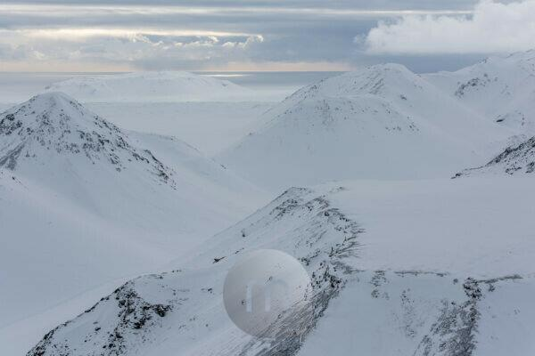 Iceland, bird's eye view, untouched snow on the mountains, the Atlantic Ocean in the background
