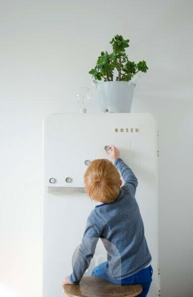DIY, Blumentopf auf Kühlschrank, Kind befestigt Kühlschrankmagneten aus Kronkorken
