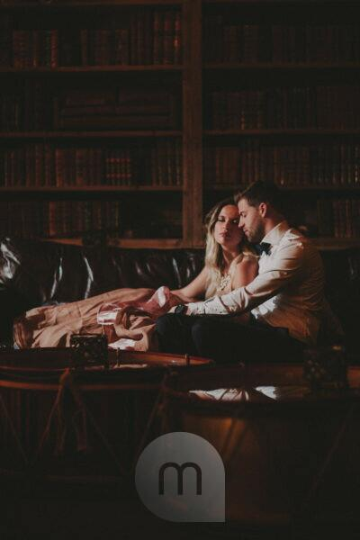 Young couple in love sitting on the sofa in a library