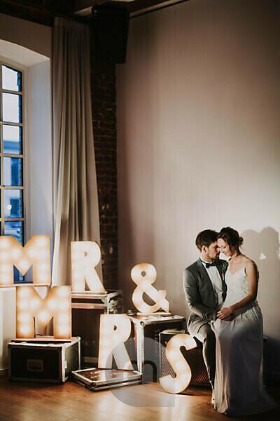 Happy bridal couple, sitting, decoration, illuminated letters