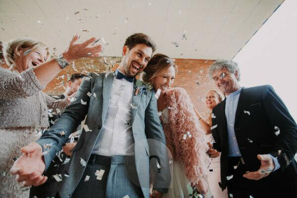 Wedding, bridal couple and guests celebrate with confetti