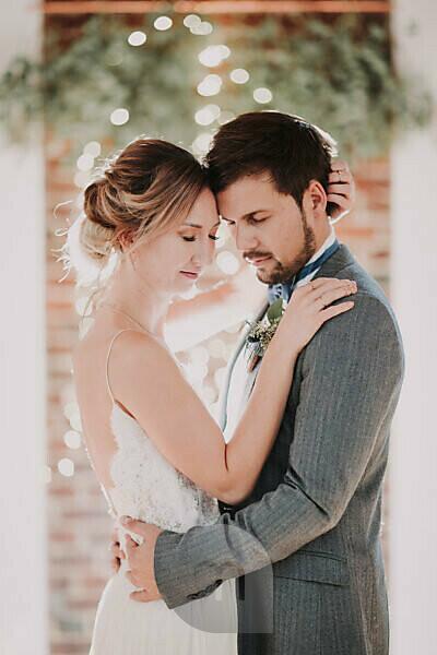 Happy bridal couple, hug, closed eyes, half portrait, side view,