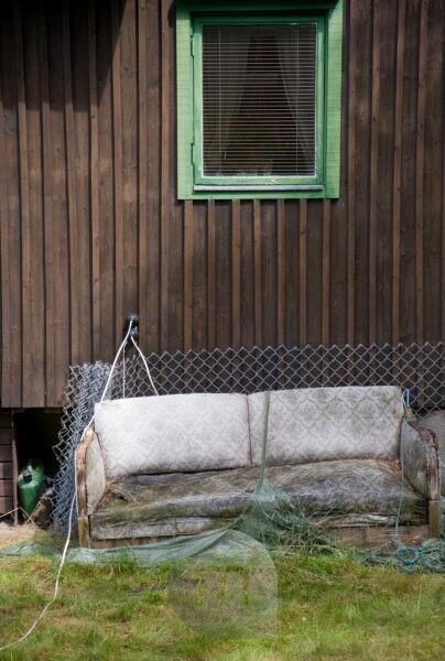 old sofa in front of wooden hut