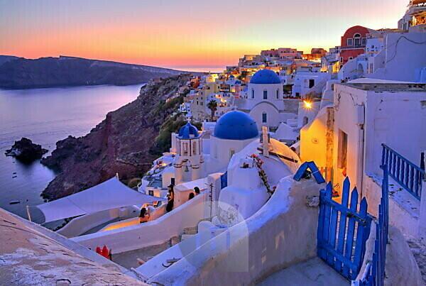 Ortsansicht mit Kirchen am Hang über der Caldera, Ia, ( Oia ), Santorin, ( Thira ), Kykladen, Ägäische Inseln, Ägäis, Griechenland, Abenddämmerung