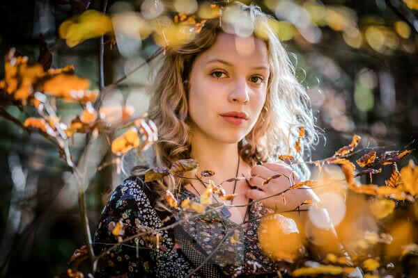 young woman with blond hair in the forest, serious and thoughtful look