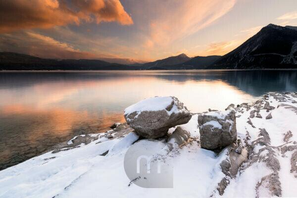 Rocks on the shore of Walchensee in the Bavarian Alps in winter with snow and evening light.